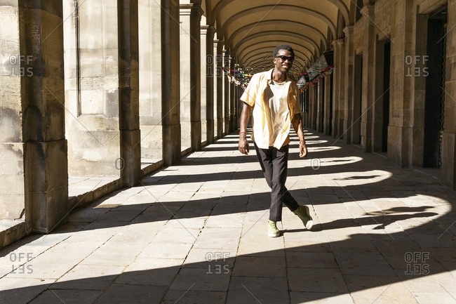 Full body of young ethnic male in summer outfit standing in arched passage and looking at camera during city stroll at weekend