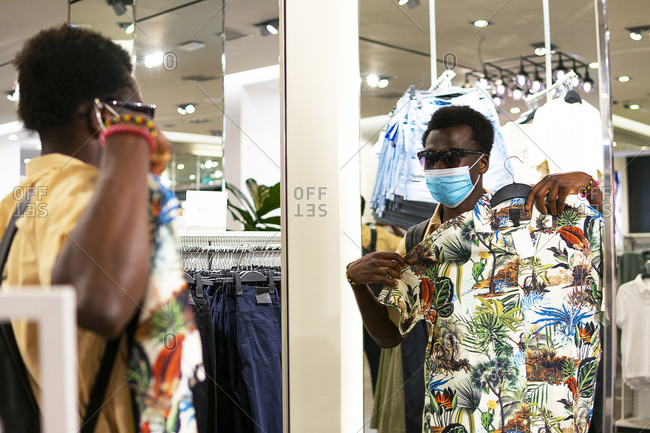 Young African American male in trendy outfit and medical mask standing in front of mirror in modern boutique and picking goods in shop during coronavirus