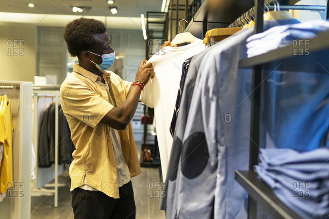 Side view of African American male in medical mask standing in clothing store and choosing t shirt during coronavirus epidemic