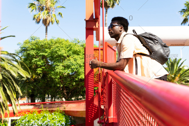 Side view of serene African American male tourist in summer wear standing on metal bridge and admiring cityscape of Barcelona during vacation