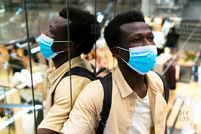 Calm African American male customer in medical mask standing near mirrored wall in modern shopping center and looking away during coronavirus
