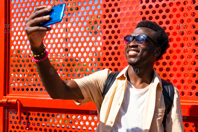 Content black male in summer wear and sunglasses standing near red metal wall and taking photo on mobile phone camera during city stroll