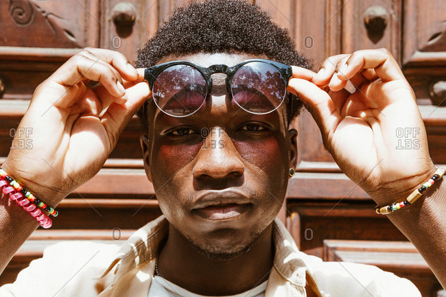 Handsome African American male with afro hairstyle and in stylish sunglasses standing near doors in city and looking at camera