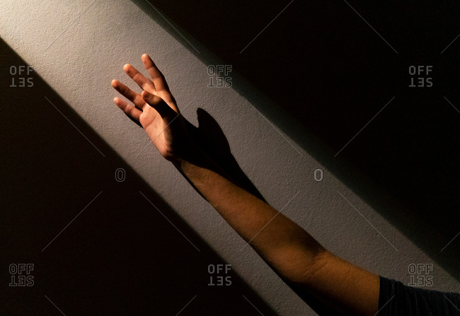 Unrecognizable crop person reaching out hand towards bright light while standing in dark room