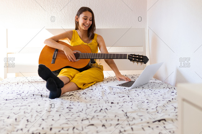 Young talented female sitting on bed with guitar and watching online tutorial on laptop