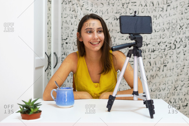 Smiling female blogger sitting at table with smartphone on tripod and recording video for social media at home