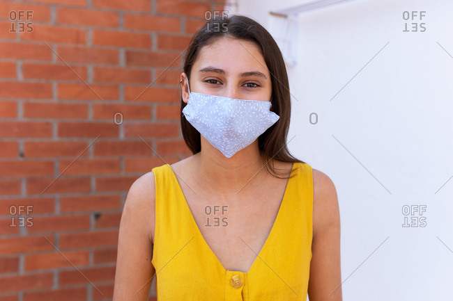 Calm female wearing protective mask standing near brick wall on street and looking at camera during coronavirus epidemic