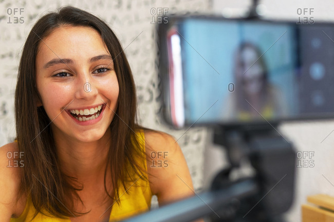 Smiling female blogger sitting at table with smartphone on tripod and recording video for social media at home looking away