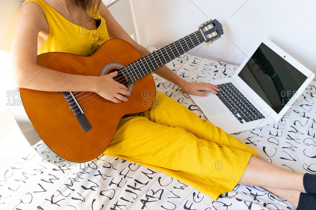 Cropped unrecognizable talented female sitting on bed with guitar and watching online tutorial on laptop