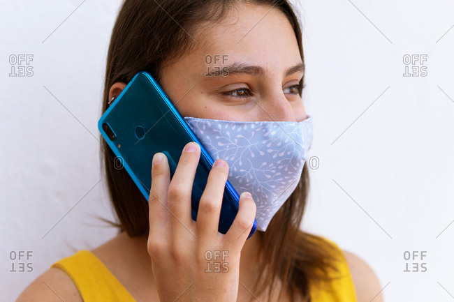Calm female wearing medical mask standing on street and speaking on mobile phone during coronavirus pandemic while looking away