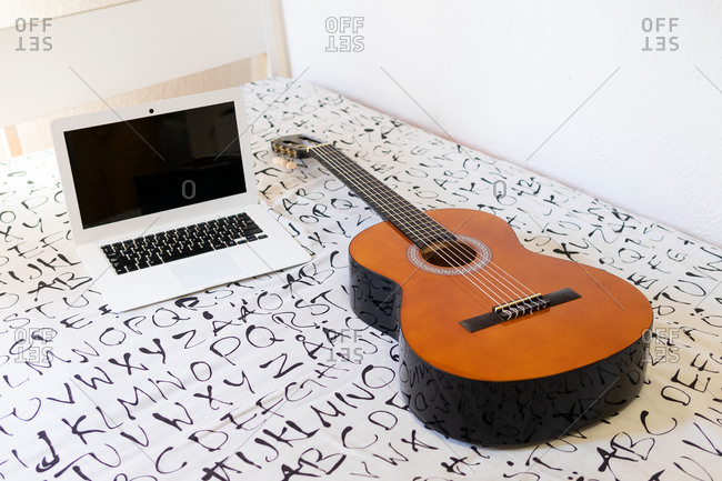 Opened modern netbook placed on soft bed with shiny acoustic guitar in bright bedroom