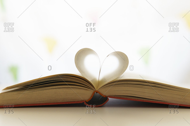 Closeup of opened book with pages in shape of heart placed on table in bright room