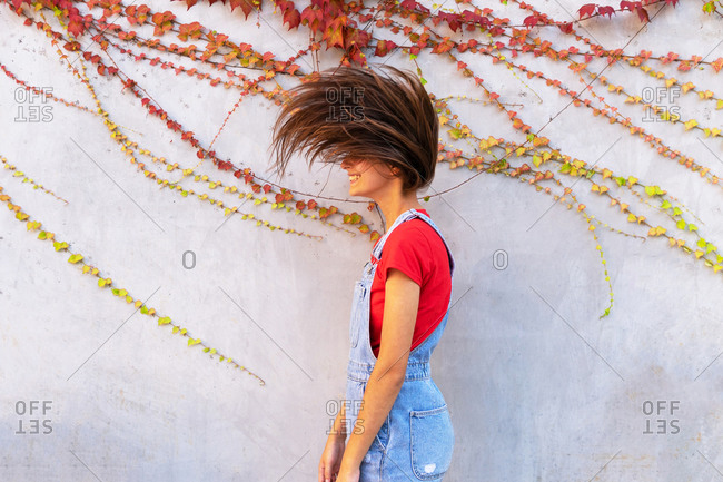 Side view of young cheerful female with flying hair standing near stone wall