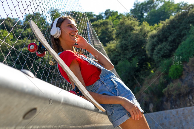 From below of content female millennial standing on street and enjoying music in wireless headphones while relaxing during weekend