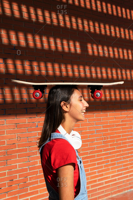 Side view of female millennial standing with skateboard on head near brick wall and laughing while having fun