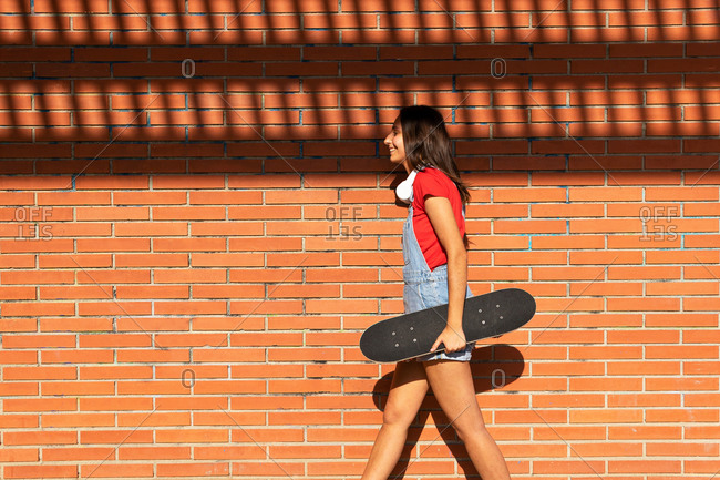 Side view of female millennial walking with skateboard near brick wall and laughing while having fun