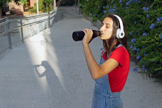 Calm female millennial standing on street in headphones and enjoying fresh water while listening to music in summer