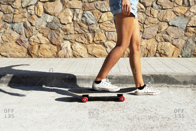 Side view of crop anonymous woman in shorts and sneakers standing on skateboard on asphalt road during sunny day in summer