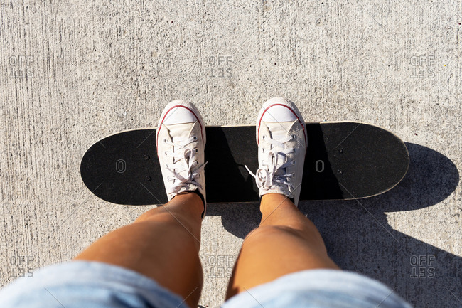 From above of crop anonymous woman in shorts and sneakers standing on skateboard on asphalt road during sunny day in summer
