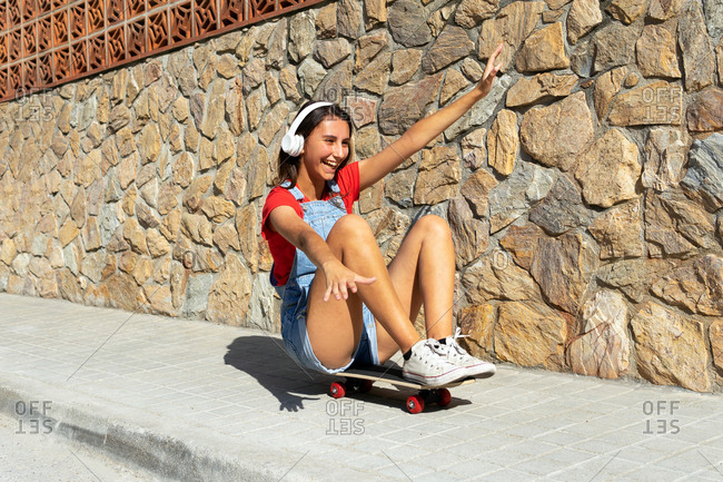 Delighted female millennial in headphones sitting on skate and riding along pavement while having fun in city in summer