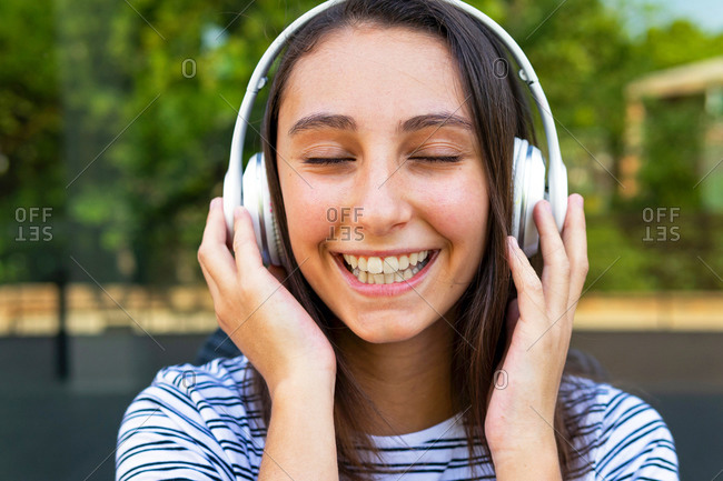 Carefree female standing near glass building and enjoying songs in wireless headphones with closed eyes