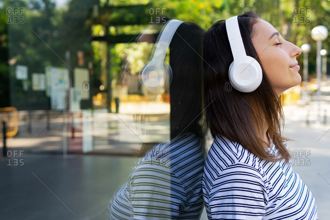 Side view of carefree female standing near glass building and enjoying songs in wireless headphones with closed eyes