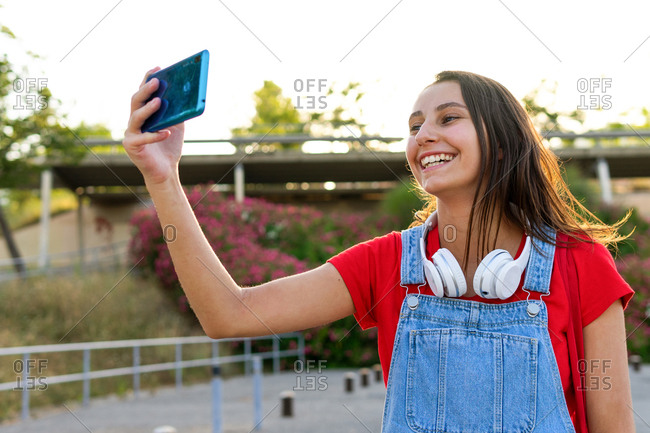 Smiling female millennial standing in city and taking photo on cellphone selfie camera