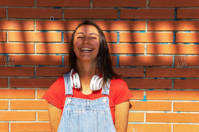 Cheerful female millennial in overalls and with wireless headphones leaning on wall and smiling at camera