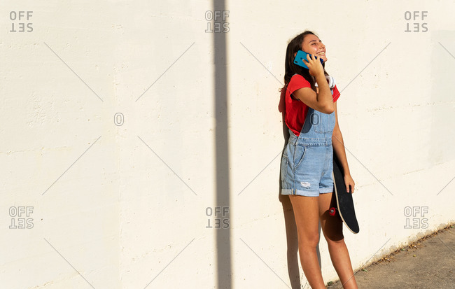 Content female skater standing with skateboard near stone wall and speaking on cellphone while entertaining during weekend in city