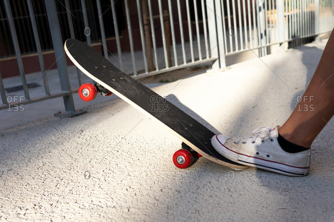 Unrecognizable millennial standing on skateboard on asphalt road during sunny day in summer