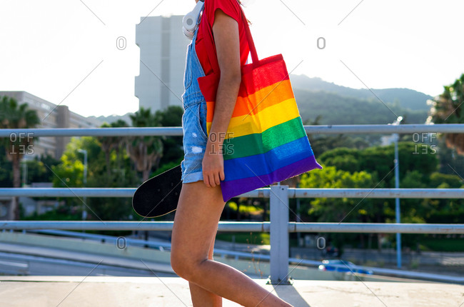 Side view of young female with rainbow shopper and skateboard walking along street on sunny day