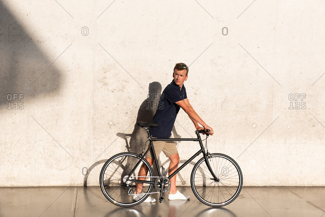 Side view of casual dressed young man walking with his urban bicycle near concrete wall