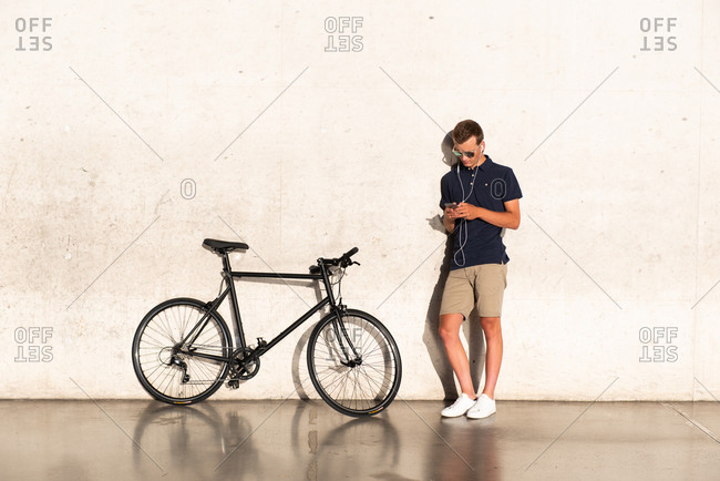 Young man using mobile phone with his bicycle leaning against concrete wall