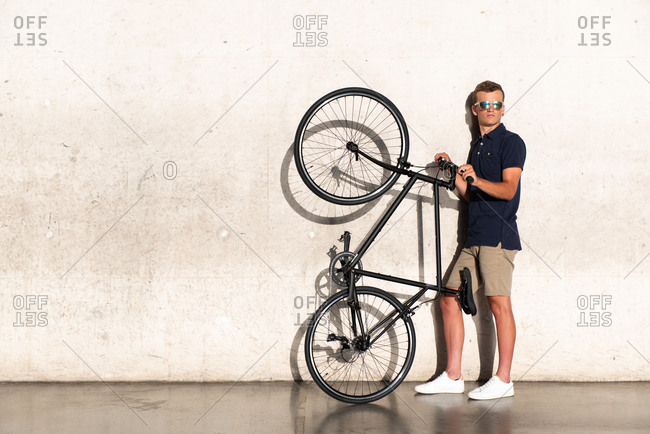 Young man with sunglasses holding his urban bicycle while leaning against concrete wall looking at camera