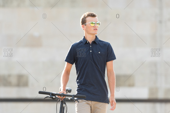 Serious casual dressed young man in sunglasses walking with his urban bicycle and looking away