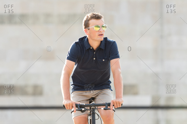 Serious casual dressed young man in sunglasses riding his urban bicycle and looking away