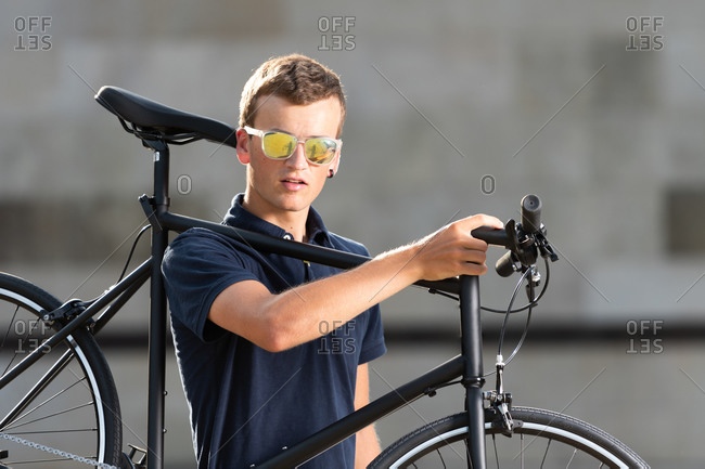 Young man with sunglasses carrying his urban bicycle on shoulder on the street looking at camera