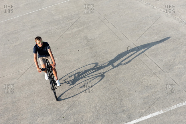 From above serious casual dressed young man in sunglasses riding his urban bicycle and looking away