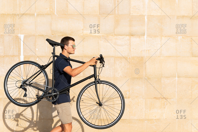 Young man with sunglasses carrying his urban bicycle on shoulder on the street looking away