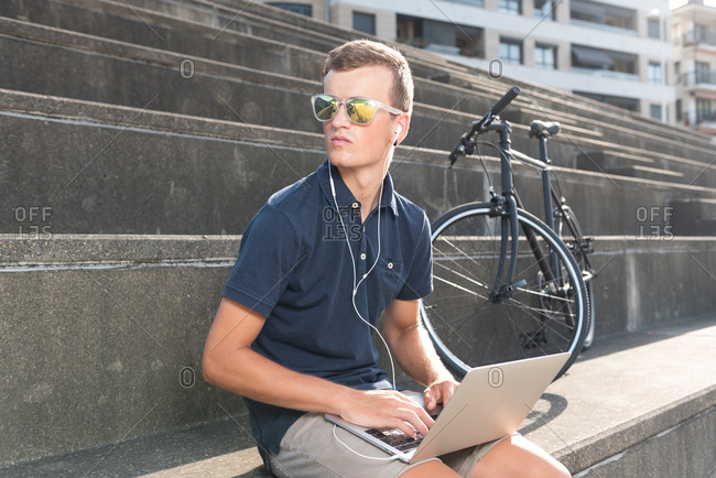 Young entrepreneur working outdoors on his laptop with his bicycle sitting on concrete stairs looking away