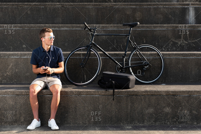 Young man using mobile phone with his bicycle sitting on concrete stairs