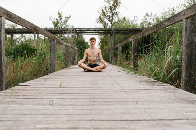 Tranquil male sitting with crossed legs in Padmasana and practicing mindfulness while doing yoga on wooden promenade