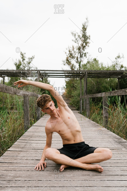 Calm male siting in Lotus pose with side bend on wooden terrace and practicing yoga