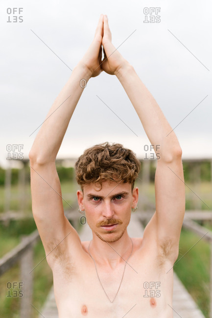 Serene male with naked torso practicing yoga in Vrksasana with Namaste gesture while looking at camera on wooden terrace in village
