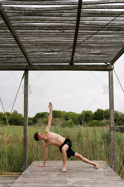 Peaceful male with naked torso standing in Vasisthasana and balancing while practicing yoga on wooden terrace and looking up