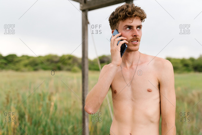 Handsome male with naked torso standing in countryside in summer talking on cellphone during weekend