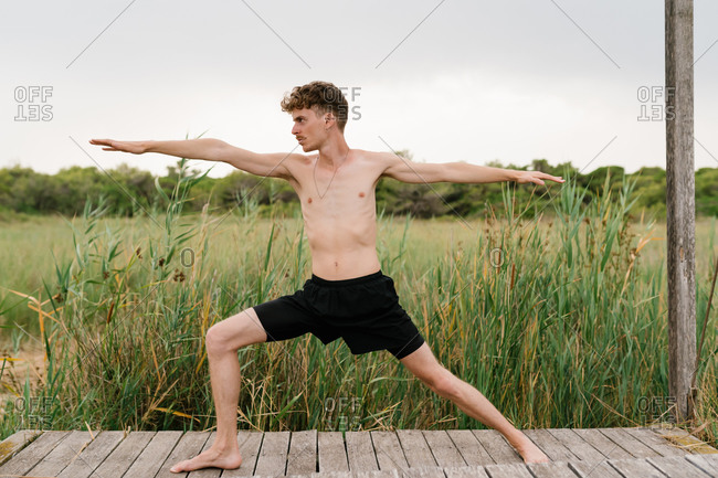 Side view peaceful male with naked torso standing in warrior two pose while practicing yoga on wooden terrace