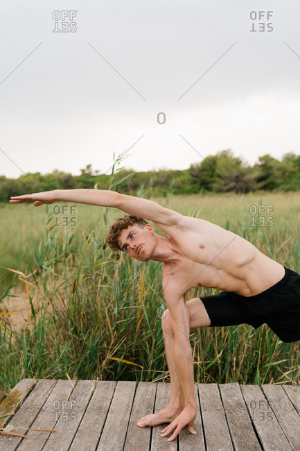 Peaceful male with naked torso standing in revolved side angle pose while practicing yoga on wooden terrace