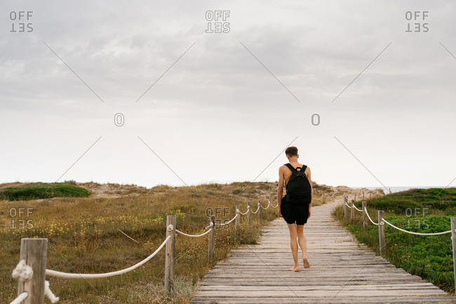 Back view of unrecognizable shirtless male in black shorts with backpack walking near fenced path amidst field in cloudy summer day in countryside