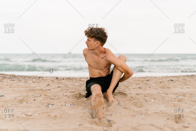 Full body of slim shirtless man sitting in Noose yoga asana during practice on sandy beach near sea
